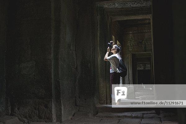 Kambodscha  Siem Reap  Angkor Thom  Touristen fotografieren Bayon-Tempel mit Kamera