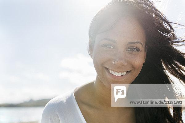 Portrait einer lächelnden jungen Frau mit Nasenpiercing im Gegenlicht