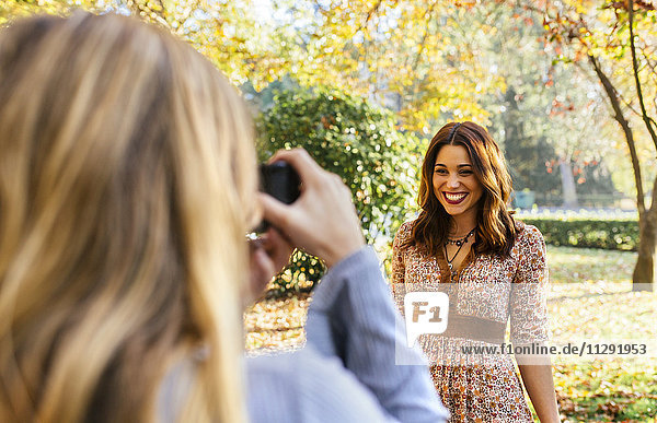 Two young women taking pictures in a park in autumn