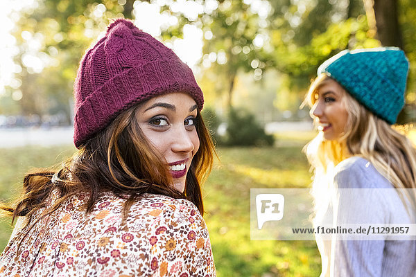 Two young women wearing wooly hats in a park in autumn