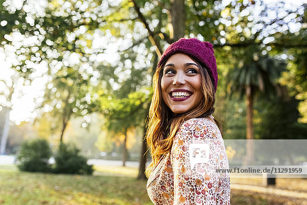 Happy young woman wearing wooly hat in a park in autumn