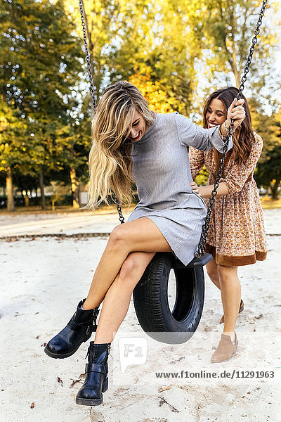 Two playful young women on a tire swing