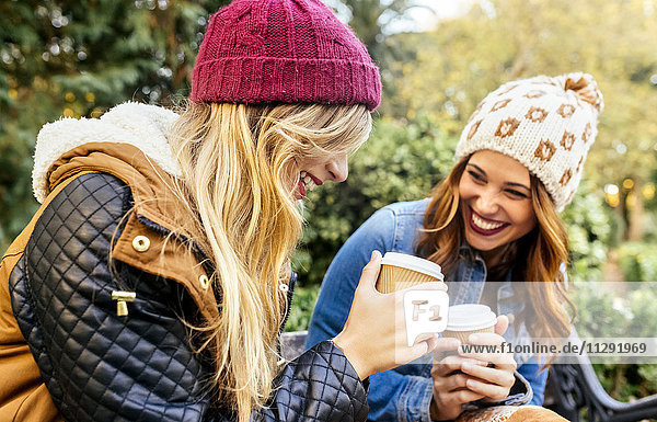 Two happy young women drinking coffee in a park in autumn