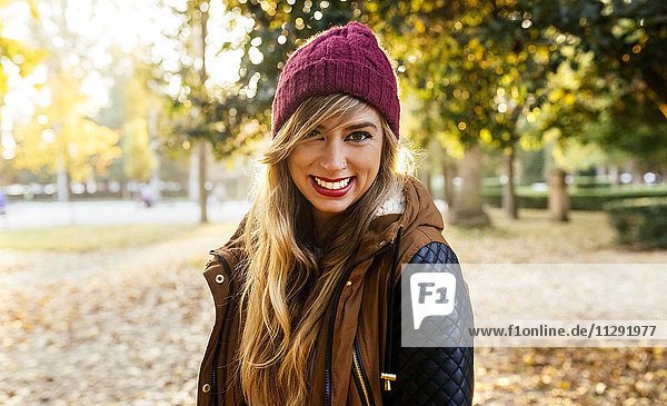 Portrait of smiling young woman wearing wooly hat in a park in autumn