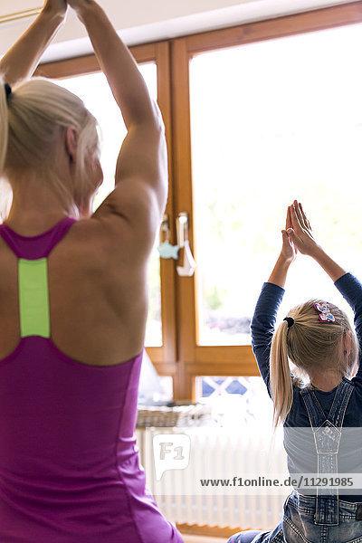 Rückansicht des kleinen Mädchens und ihrer Mutter beim Yoga im Wohnzimmer