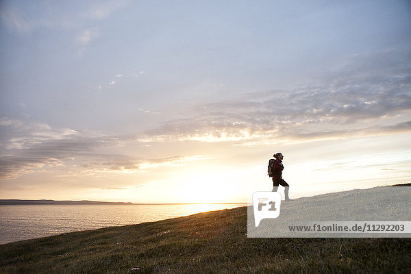 Iceland  woman hiking upon a hill at twilight