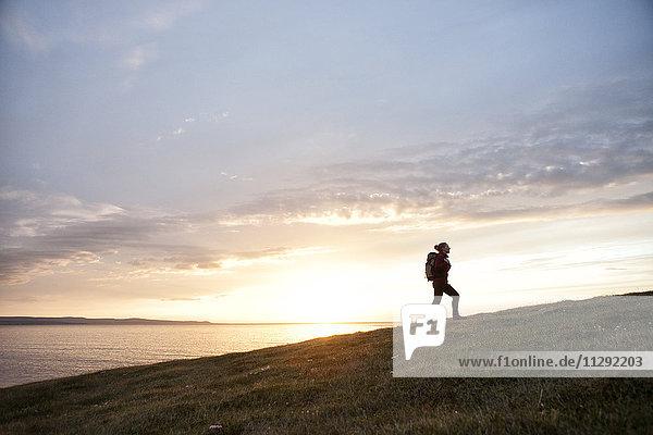 Island  Frau beim Wandern auf einem Hügel in der Dämmerung