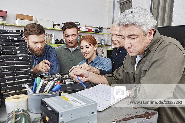 Mann durchläuft Checkliste in Computer-Recyclinganlage