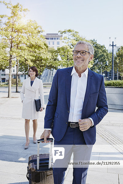 Lächelnder Geschäftsmann unterwegs mit Geschäftsfrau im Hintergrund