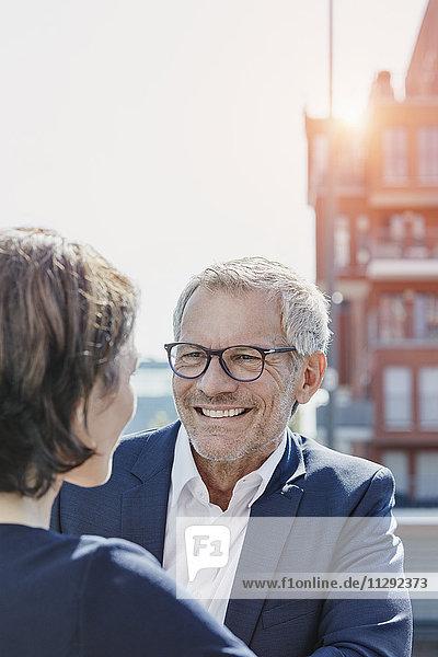 Geschäftsmann und Geschäftsfrau im Gespräch im Freien