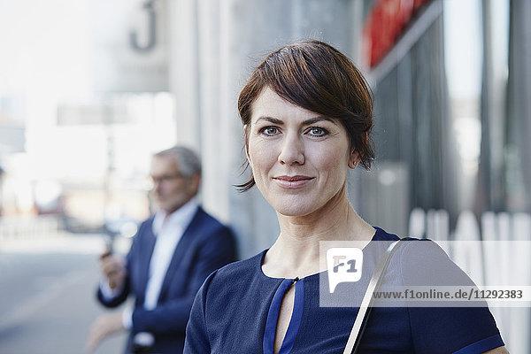 Porträt einer Geschäftsfrau mit Geschäftsmann im Hintergrund