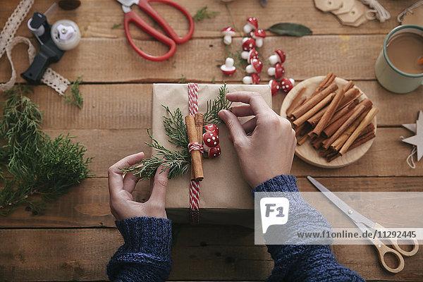 Frauenhände schmücken Weihnachtsgeschenk