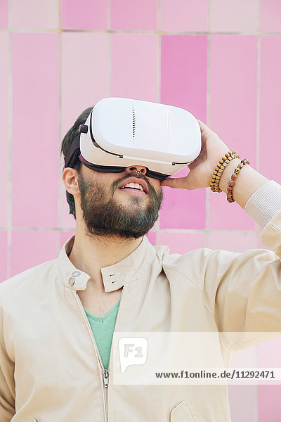 Man wearing Virtual Reality Glasses in front of the pink wall
