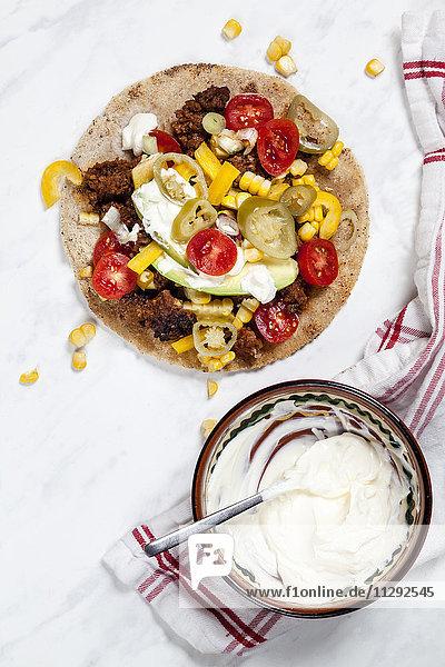 Mexikanische Tortilla mit Hackfleisch  Avocado  Tomaten  Mais  Jalapeno-Pfeffer und Sauerrahm