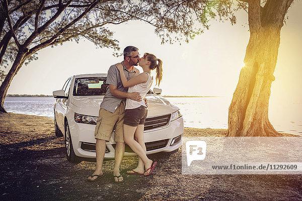 Paar auf einem Roadtrip  das eine Pause macht und sich küsst.