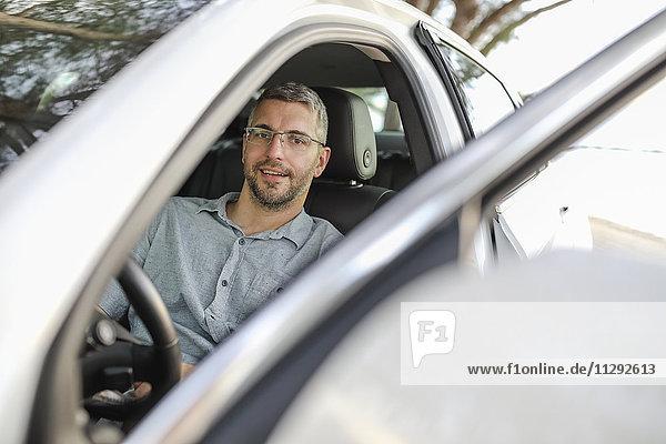 Mann im Auto sitzend  eine Pause machend