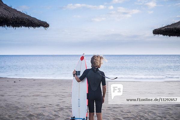 Spanien  Teneriffa  Junge mit Surfbrett am Strand