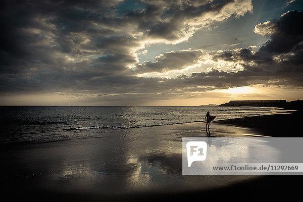 Spanien  Teneriffa  Junge mit Surfbrett am Strand bei Sonnenuntergang Spanien, Teneriffa, Junge mit Surfbrett am Strand bei Sonnenuntergang