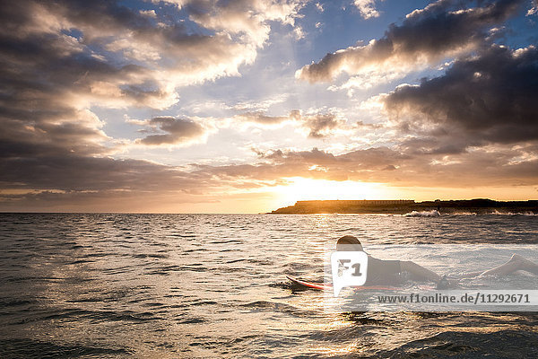 Spanien  Teneriffa  Junge beim Surfen im Meer bei Sonnenuntergang