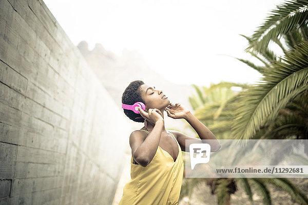 Spanien  Frau mit geschlossenen Augen Musik hören mit rosa Kopfhörern