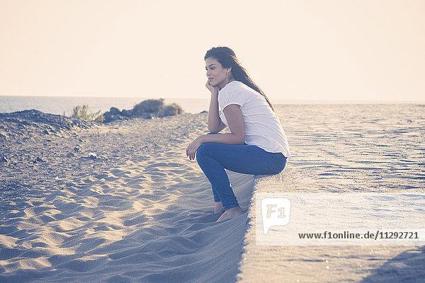 Junge Frau am Strand sitzend