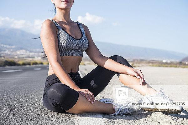 Junge sportliche Frau  die eine Pause macht  auf der Straße sitzend