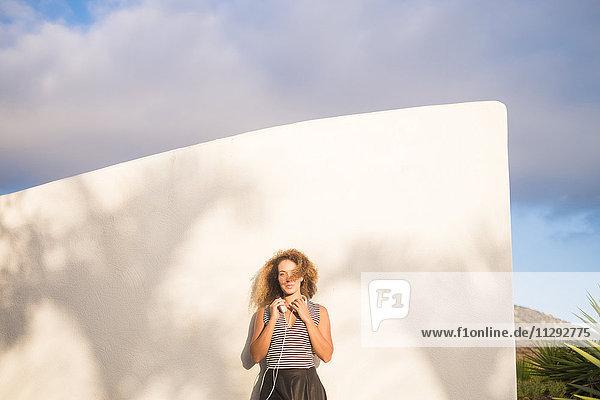 Junge Frau mit Kopfhörern  die sich bei Sonnenlicht an die Wand lehnen.