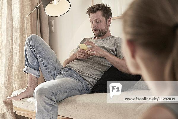 Mann zu Hause auf der Couch sitzend mit Blick auf Handy und Frauen im Vordergrund