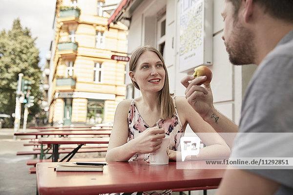 Lächelnde Frau  die den Mann in einem Straßencafé ansieht.