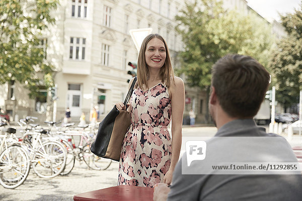 Lächelnde Frau  die in einem Straßencafé ankommt und den Mann ansieht.