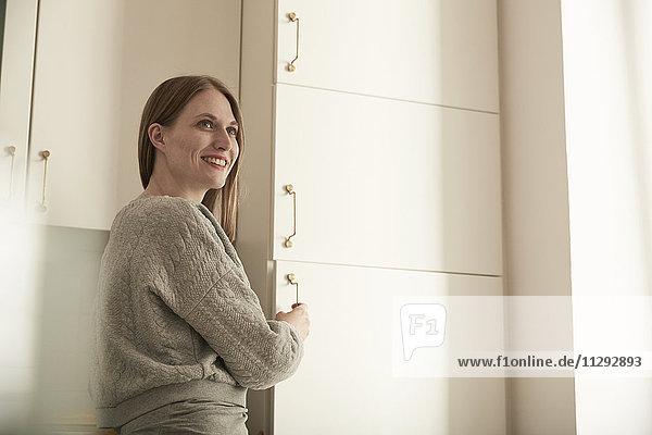 Lächelnde Frau in der Küche am Kühlschrank