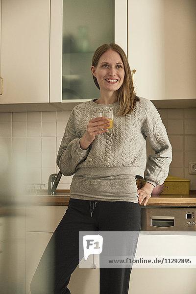 Lächelnde Frau trinkt Saft in der Küche
