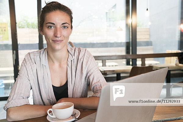 Porträt einer lächelnden jungen Frau mit Tasse Kaffee und Laptop in einem Coffee-Shop