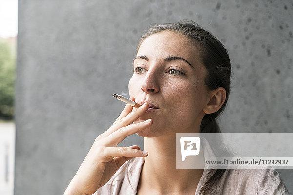 Porträt der rauchenden jungen Frau