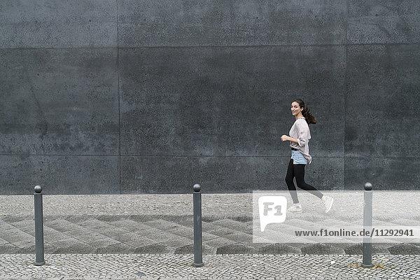 Junge Frau  die in der Stadt läuft