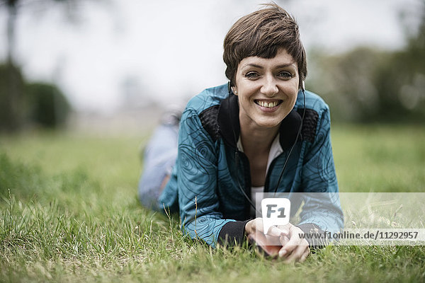 Portrait of smiling young woman lying on a meadow listening music with earphones