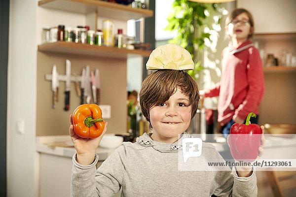 Porträt eines lächelnden Jungen in der Küche mit halb Weißkohl auf dem Kopf und Paprika in den Händen.