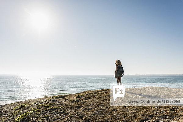 Rückansicht der Teenagerin  die in der Abenddämmerung mit dem Smartphone am Meer fotografiert.