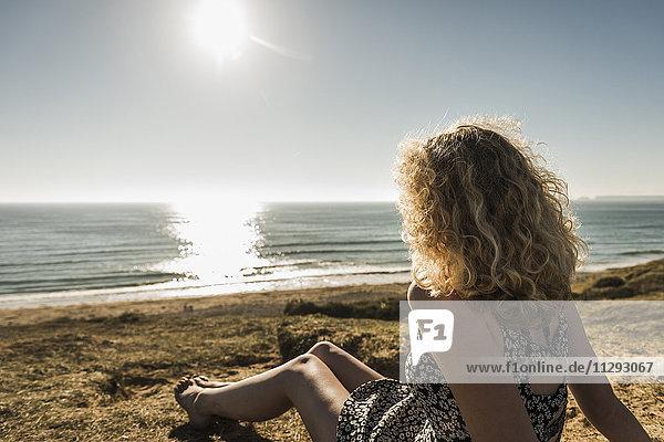 Rückansicht des Mädchens am Strand in der Abenddämmerung mit Blick aufs Meer
