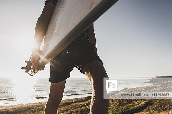 Teenager Junge mit Surfbrett am Meer  Teilansicht