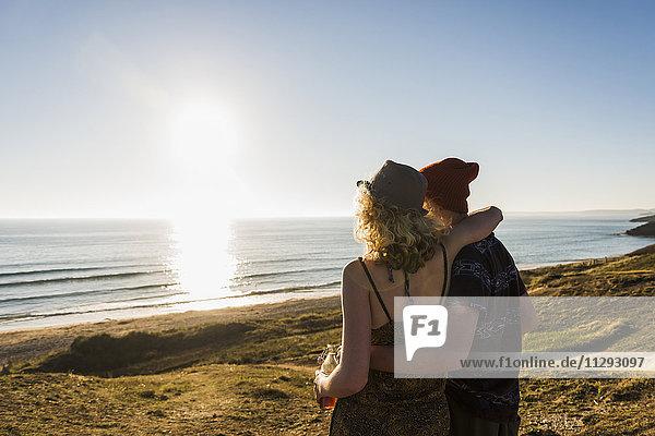 Rückansicht des jungen Paares am Meer