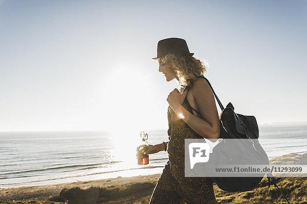 Blondes Teenagermädchen mit Rucksack und Getränk am Meer in der Abenddämmerung
