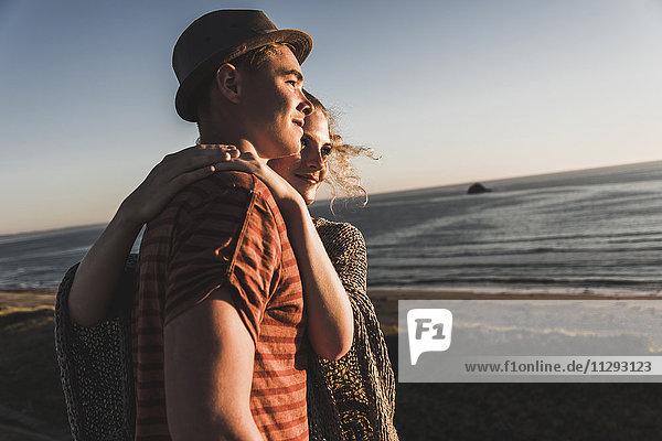 Verliebtes junges Paar beim Sonnenuntergang am Strand