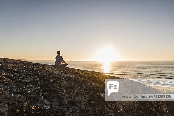 Rückansicht einer Frau  die bei Sonnenuntergang auf einer Klippe meditiert.