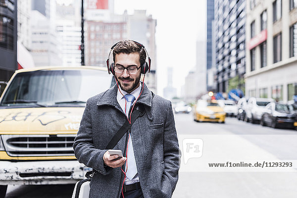 USA  New York City  businessman with cell phone and headphones on the go