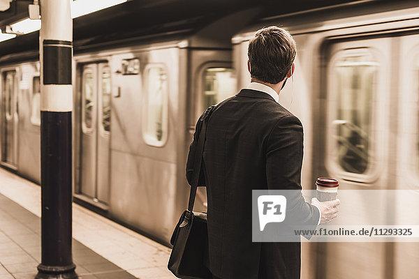 Junger Geschäftsmann wartet am Bahnsteig der U-Bahn-Station und hält Einwegbecher