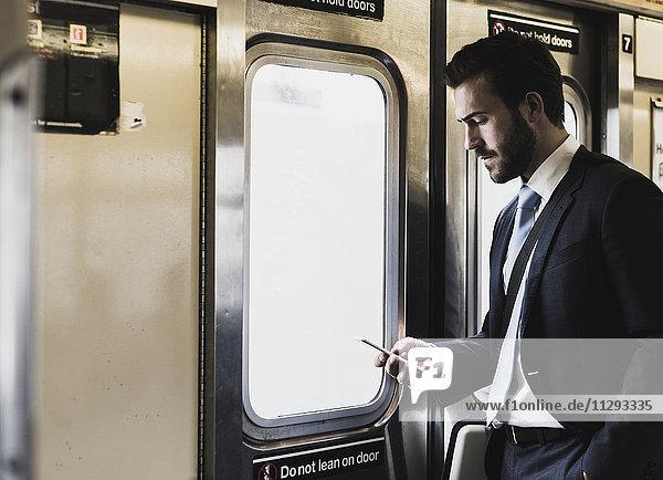 Young businessman taking metro  using smart phone