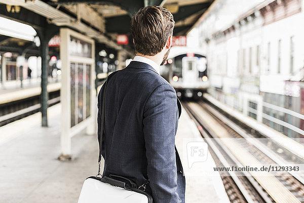 Junger Geschäftsmann wartet am Bahnsteig der U-Bahn-Station