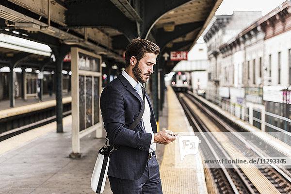 Junge Geschäftsleute warten am Bahnsteig der U-Bahn  mit Smartphone