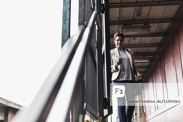 Reife Frau mit Smartphone am S-Bahnhof